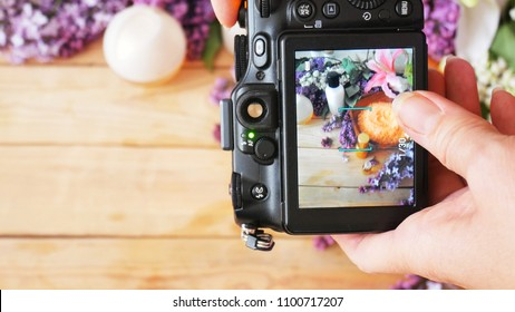 takes a photo with still life with lilac flowers and cream cosmetic by photo camera