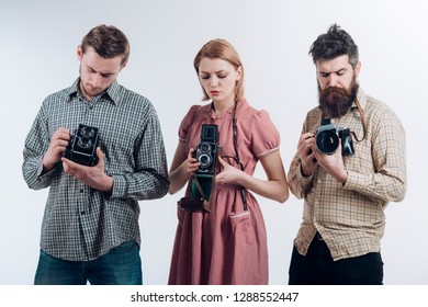 Taking another shot. Paparazzi or photojournalists with vintage old cameras. Retro style woman and men hold analog photo cameras. Group of photographers with retro cameras. Photography studio.