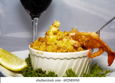 Taking a bite of Lobster Macaroni and Cheese served with a glass of red wine