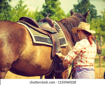 Taking care of animals, horsemanship, equine concept. Cowgirl getting horse ready for ride on countryside.