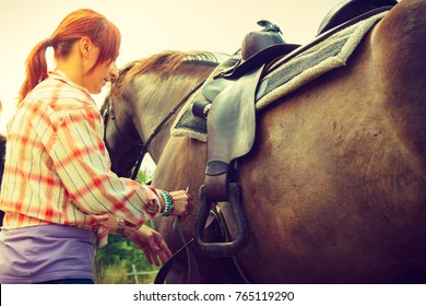 Taking care of animals, horsemanship, equine concept. Redhead cowgirl getting horse ready for ride on countryside.