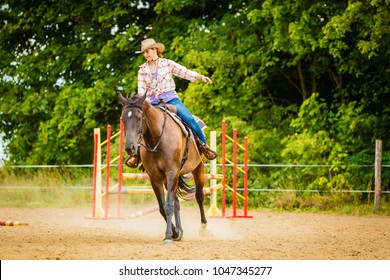 Taking care of animals, horsemanship, western competitions concept. Cowgirl doing horse riding on countryside meadow, sunny day outside