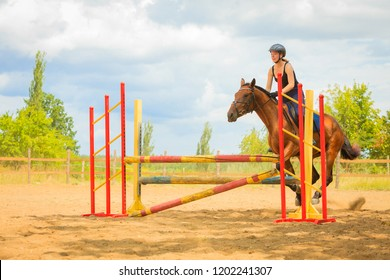 Taking care of animals, horsemanship, western competitions concept. Jockey young girl doing horse jumping through hurdle on sunny day
