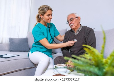Taking care of health. Selective focus on a serene retired gentleman sitting on a sofa while a female nurse using her stethoscope and listening to his lungs.