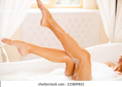 Taking care of her beautiful legs. Side view of beautiful young woman touching her leg while enjoying luxurious bath