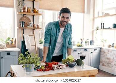Taking care of his health. Handsome young man in casual wear looking at camera and smiling while standing in the kitchen at home