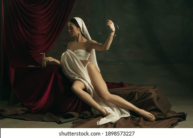 Taking care. Modern remake of classical artwork with coronavirus theme - young medieval woman on dark background posing with medicine snake and pills. Concept of coronavirus, pandemic, creativity.