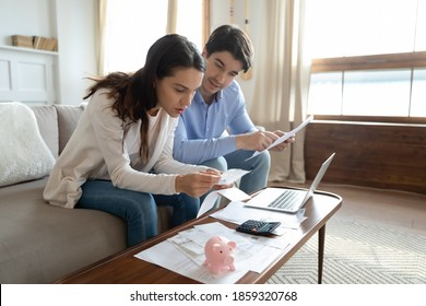 Taking close look at paper. Concentrated attentive millennial couple sitting at home office in living room involved in reading documents preparing to provide loan mortgage utility bills payment online