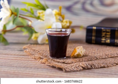 Taking communion concept - the wine and the bread symbols of Jesus Christ blood and body with Holy Bible. Easter Passover and Lord Supper concept Focus on glass.