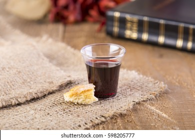 Taking Communion. Cup of glass with red wine, bread and Holy Bible on wooden table close-up. Focus on bread