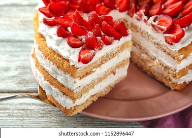 Taking of delicious strawberry cake from plate by using shovel, closeup