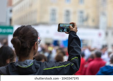 Taking Digital Photograph with Smartphone during Public City Marathon Sport Event.