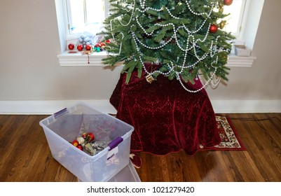 Taking down the Christmas tree....Most ornaments gone with plastic container holding some on floor by tree