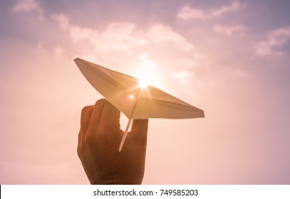 Taking flight! Dreams and imagination. Hand throwing paper airplane.