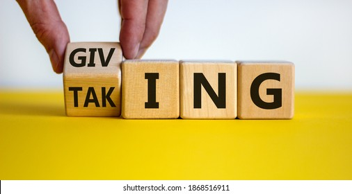 Taking or giving symbol. Hand turns a cube and changes the word 'taking' to 'giving' on wooden cubes. Beautiful yellow table, white background, copy space. Business and taking or giving concept.