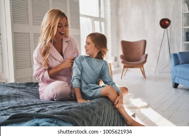 Taking good care of her. Beautiful young mother brushing her daughters hair while sitting on the bed at home
