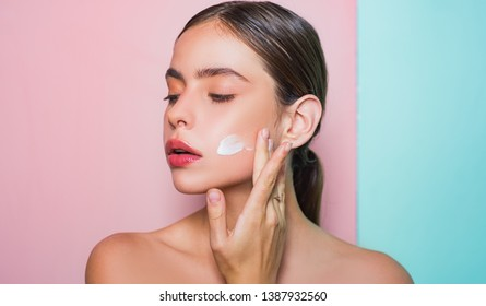 Taking good care of her skin. Beautiful woman spreading cream on her face. Skin cream concept. Facial care for female. Keep skin hydrated regularly moisturizing cream. Fresh healthy skin concept.