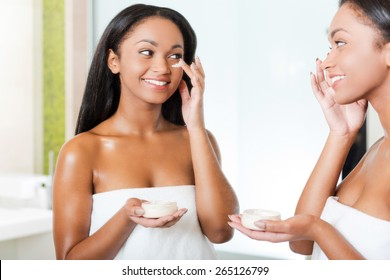 Taking good care of her skin. Beautiful young African woman spreading cream on her face and smiling while standing against a mirror in bathroom