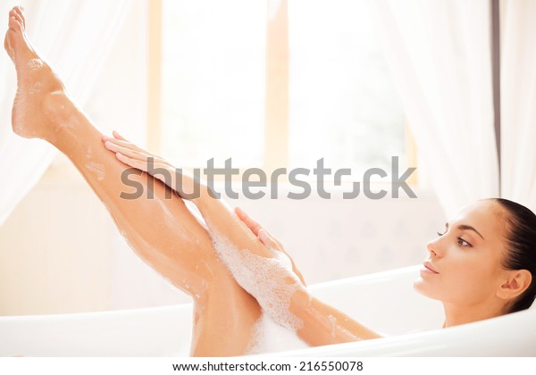 Taking good care of her skin. Side view of attractive young woman touching her leg while enjoying luxurious bath