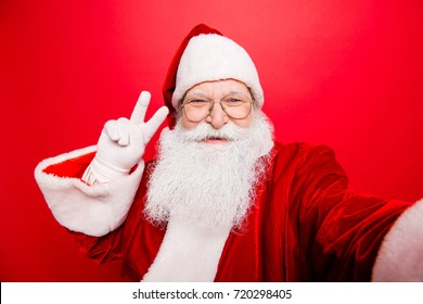 Taking holly jolly x mas festive memories. Funny Saint Nicholas photographer in red traditional outfit, head wear is showing peace gesture and makes shot on camera, isolated on red background