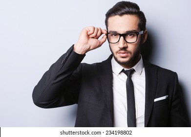 Taking life seriously. Portrait of handsome young man in formalwear adjusting his glasses while standing against grey background