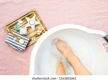 Taking a magnesium footbath for better absorbent of vitamin mineral magnesium chloride. Soaking feet in relaxing foot bath, wooden tray with ingredients on the side. Great for pregnant women.