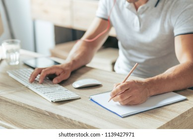 Taking notes. Close up of a notebook lying on the table while being used for writing notes