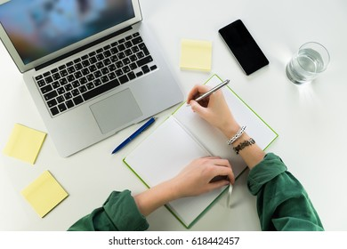 Taking notes in copybook at home working place. Top view of female person hands writing in note book sitting at white table with smartphone, portable computer and glass of water
