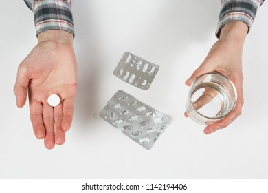 Taking one pill with a glass of drinking water on white background isolated