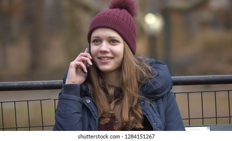 Taking a phone call while sitting on a bench at Central Park New York