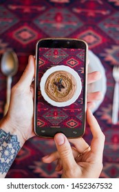 Taking phone food photo in restaurant. Smartphone lunch photography at cafe. Hands tap screen.