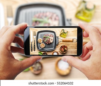 Taking photo of beef steak by smartphone. Closeup view of  process. File contains clipping paths for smartphone and hands and  picture on it.