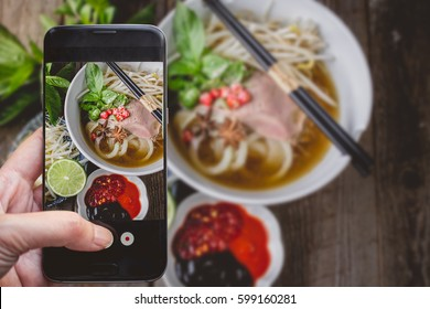 Taking a photo by Finger Pressing on Smartphone for Photograph Pho Vietnamse Noodle Soup on Wooden Background with Copy Space. Image for Food Advertise Concept
