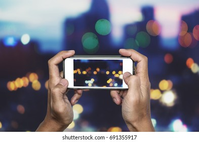 Taking photo by smart phone, Hands holding smartphone taking Bokeh lights