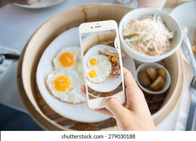 Taking photo of egg with sausages for breakfast