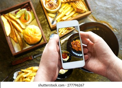 Taking photo of food with smartphone , mobile photographer