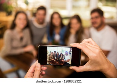 Taking a photo of a group of friends at the bar