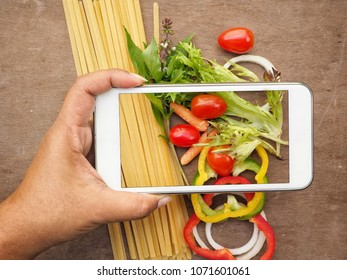 Taking a photo of italian food ingredients  with smart phones on hand
