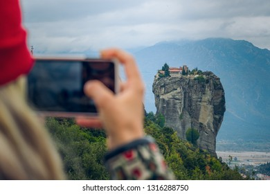 taking photo on mobile device by girl who stay back to camera, rocky dramatic picturesque landscape in Greece, wallpaper travel concept photography with empty copy space for your text