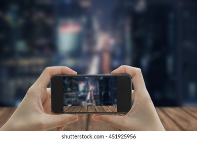 Taking photo on smart phone concept.Wooden table on  blurred  Cityscape background.