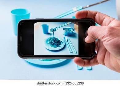 Taking photo with phone of spaghetti, plate, glass, table, fork and pot of blue color.