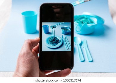 Taking photo with phone of spaghetti, plate, glass, table, fork and pot of blue color