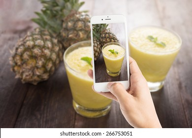 Taking photo of pineapple smoothie on wooden table.