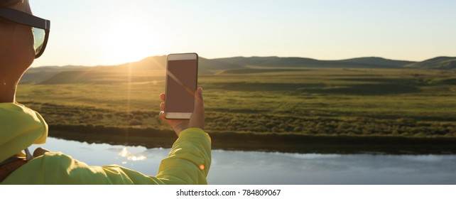 taking photo with smart phone in beautiful sunset landscape