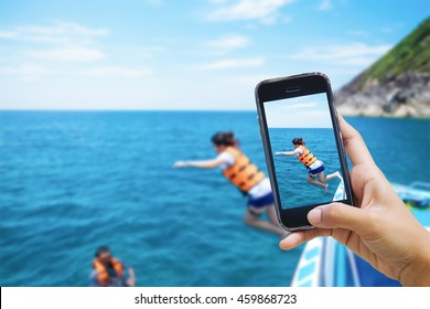 Taking photo of snorkeling divers jump in the beautiful sea-selective focus on hand and smartphone