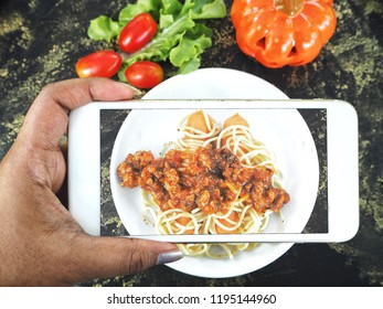 Taking a photo of spaghetti food in halloween day with smart phone on hand