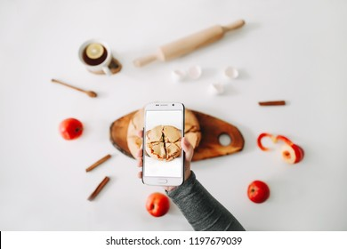 Taking photos of breakfast on phone. Composition with delicious apple pie on white background. Photo of food in instagram style. Social media concept. Fall autumn concept. Top view, flatlay