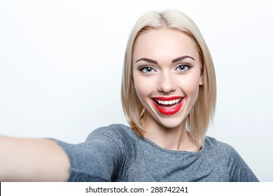 Taking picture. Smiling cheerful blond-haired woman doing selfie on isolated white background