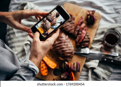 Taking a picture of some steaks and grilled vegetables with a mobile phone.