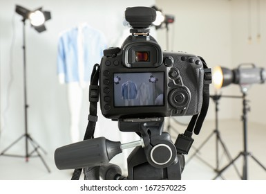 Taking pictures of ghost mannequin with modern clothes in professional photo studio, focus on camera